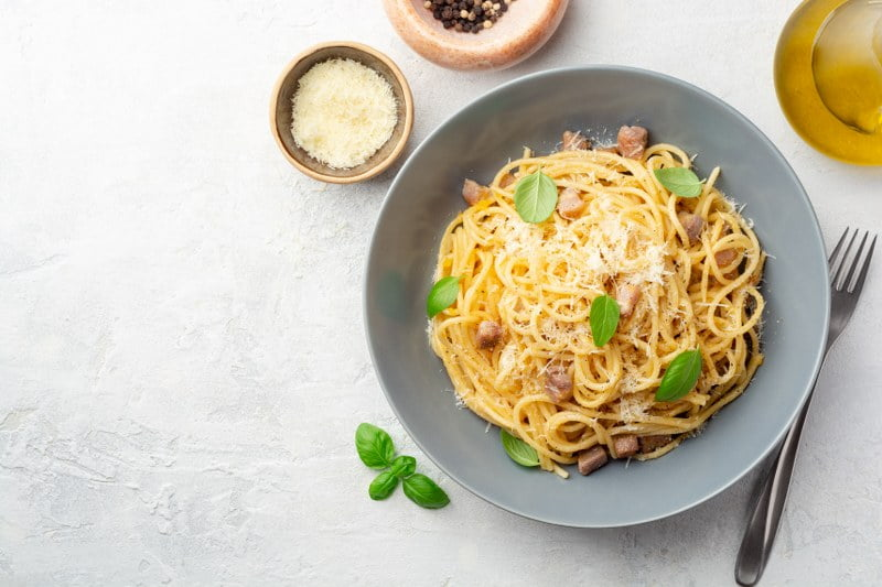 pasta carbonara in bowl with basil leaves
